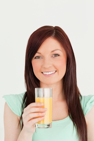 Cheerful red-haired woman enjoying a glass of orange juice in the kitchen in her appartment Stock Photo - 10205957