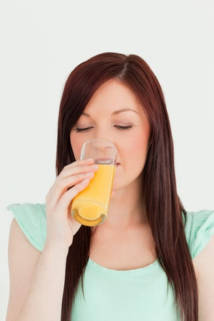 Attractive red-haired woman drinking a glass of orange juice in the kitchen in her appartment Stock Photo - 10205929