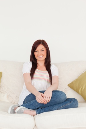 Attractive red-haired woman posing while sitting on a sofa in the living room Stock Photo - 10198851