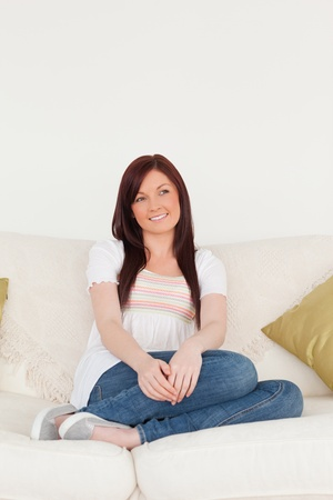 Smiling red-haired woman posing while sitting on a sofa in the living room photo