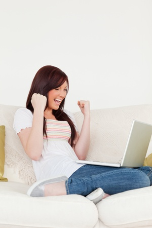 Good looking red-haired woman being joyful after gambling with her laptop while sitting on a sofa in the living room photo