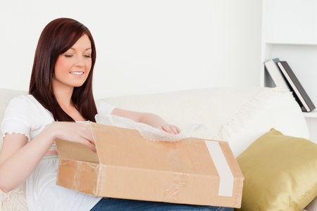 carboard box: Attractive red-haired woman opening a carboard box while sitting on a sofa in the living room