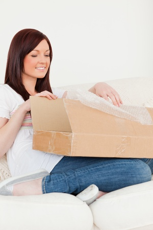 carboard box: Good looking red-haired woman opening a carboard box while sitting on a sofa in the living room