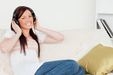 Attractive red-haired woman listening to music with headphones while sitting on a sofa in the living room photo