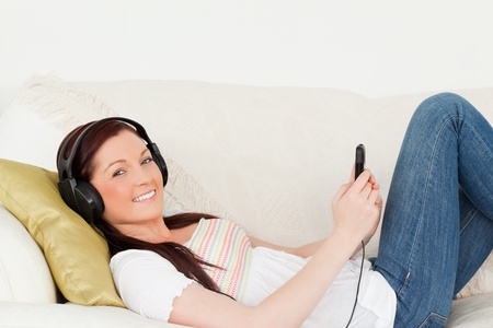 Good looking red-haired woman listening to music with headphones while lying on a sofa in the living room photo