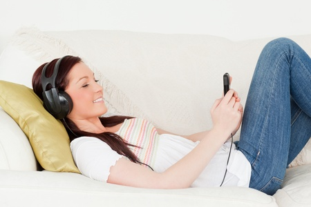 Beautiful red-haired woman listening to music with headphones while lying on a sofa in the living room Stock Photo - 10206589