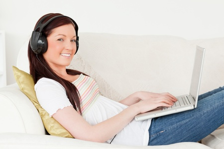 Good looking red-haired woman listening to music with headphones while relaxing with her laptop in the living room photo