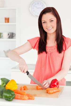 Beautiful red-haired woman cutting some carrots in the kitchen in her appartment photo
