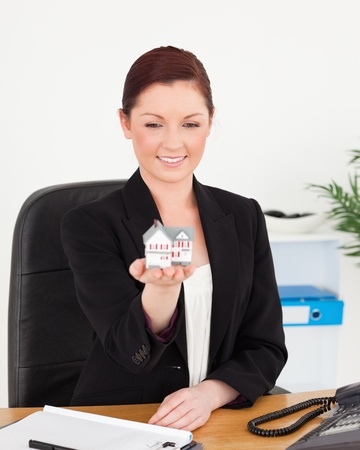 Young attractive red-haired woman in suit holding a miniature house while sitting in an office photo