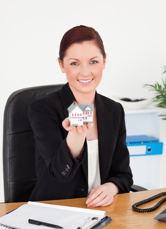Young beautiful red-haired woman in suit holding a miniature house while sitting in an office photo