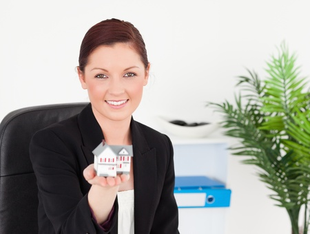 Young pretty red-haired woman in suit holding a miniature house while sitting in an office photo