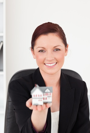 Attractive red-haired woman in suit holding a miniature house while sitting in an office photo