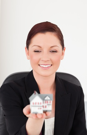 Good looking red-haired woman in suit holding a miniature house while sitting in an office photo