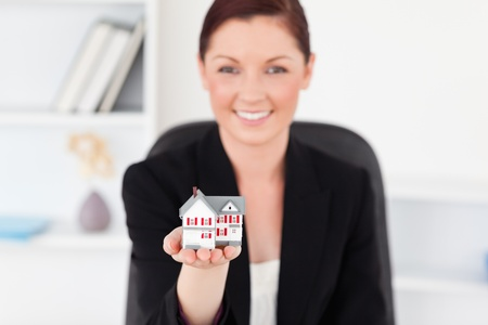 Pretty red-haired woman in suit holding a miniature house while sitting in an office photo