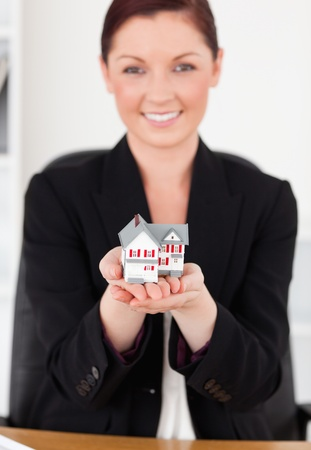 Young attractive red-haired female in suit holding a miniature house while sitting in an office photo