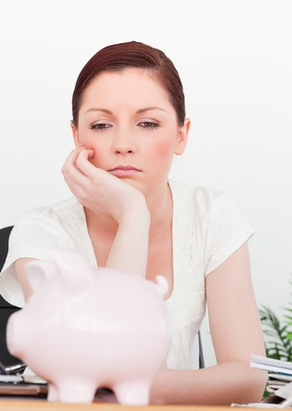 Young pensive female thinking while sitting in an office photo