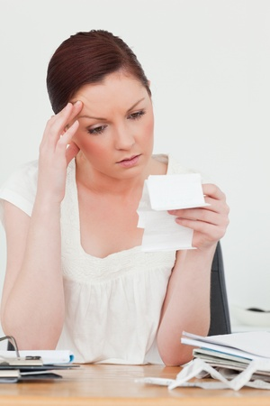 Young attractive red-haired female being depressed by the amount of the receipt while sitting at a desk Stock Photo - 10198663