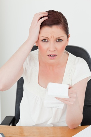 Young attractive red-haired female being scared by the amount of the receipt while sitting at a desk photo
