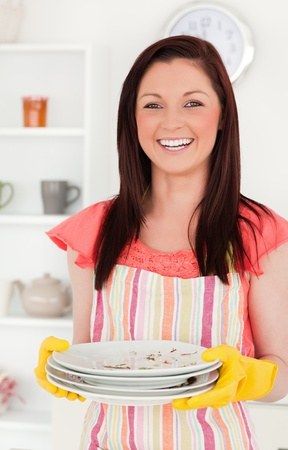Beautiful red-haired woman holding some dirty plates in the kitchen in her appartment photo