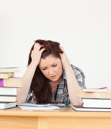 Attractive red-haired female being depressed while studying for an examination at her desk photo