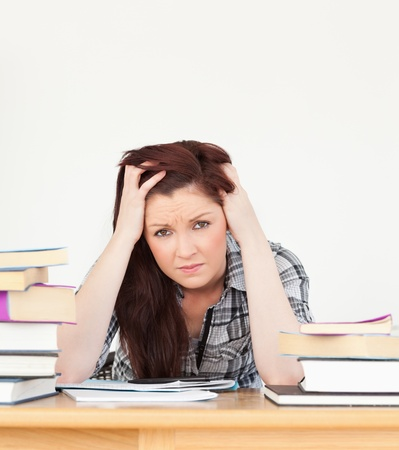 Beautiful red-haired female being depressed while studying for an examination at her desk photo