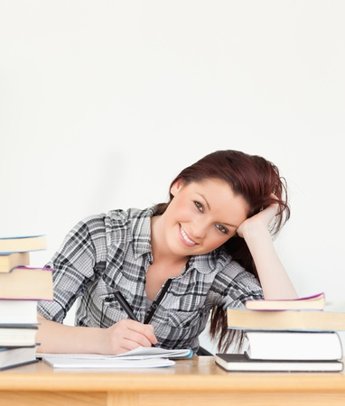 Attractive joyful red-haired girl studying for an examination at her desk Stock Photo - 10191898