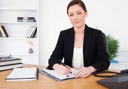 Attractive red-haired female in suit writing on a notepad and posing while sitting in an office photo