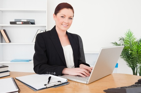 Young beautiful red-haired female in suit typing on her laptop while sitting in an office photo