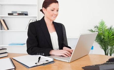 Young attractive red-haired female in suit typing on her laptop while sitting in an office photo