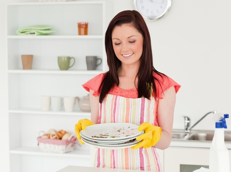 Good looking red-haired woman holding some dirty plates in the kitchen in her appartment photo