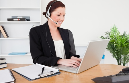Young good looking red-haired female in suit typing on her laptop and using headphones while sitting in an office photo