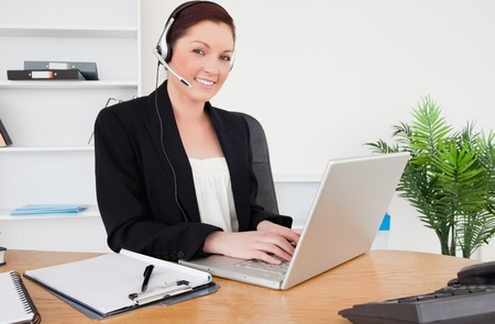 Young beautiful red-haired female in suit typing on her laptop and using headphones while sitting in an office Stock Photo - 10199017