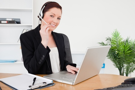 Young attractive red-haired female in suit typing on her laptop and using headphones while sitting in an office photo
