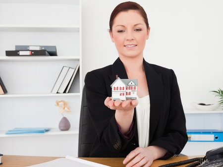 Young good looking red-haired female in suit holding a miniature house while sitting in an office photo
