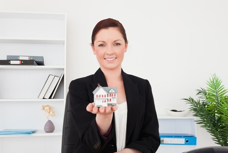 Young gorgeous red-haired female in suit holding a miniature house while sitting in an office photo