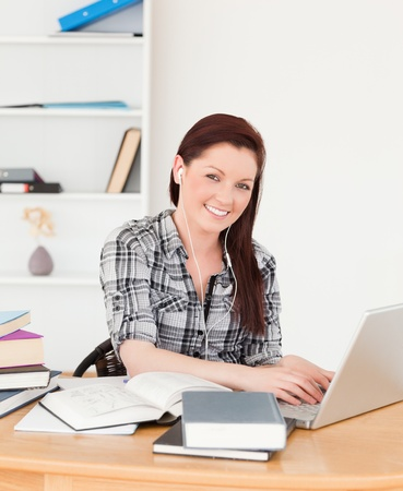Good looking joyful girl relaxing with a laptop at her desk photo