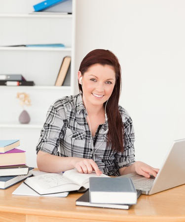 Young beautiful red-haired girl relaxing with a laptop at her desk photo