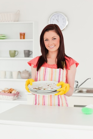 Gorgeous red-haired woman holding some dirty plates in the kitchen in her appartment photo
