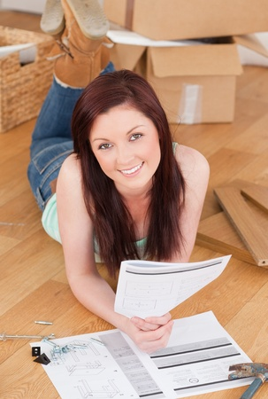 doityourself: Good looking red-haired girl posing while reading a manual before do-it-yourself at home