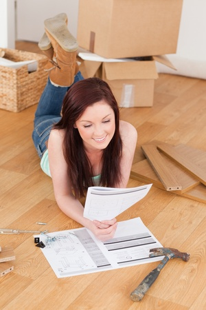 doityourself: Good looking red-haired girl reading a manual before do-it-yourself while lying on the floor at home Stock Photo