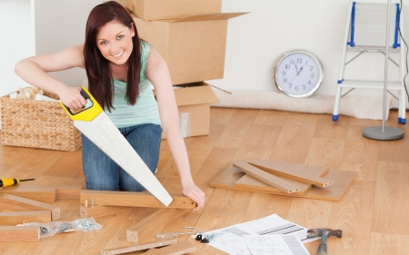 Pretty red-haired woman using a saw for diy at home photo