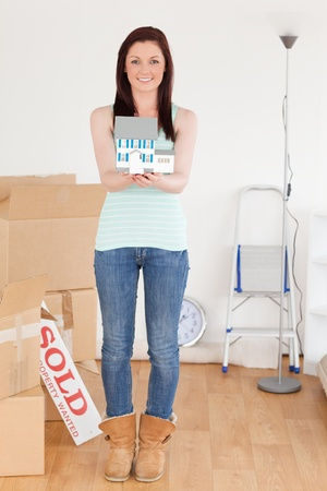 Attractive red-haired woman holding a miniature house standing on the floor at home photo
