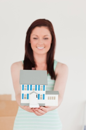 Pretty red-haired woman holding a miniature house while standing on the floor at home photo
