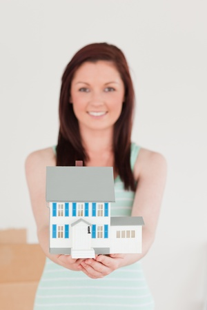 Cute red-haired woman holding a miniature house while standing on the floor at home photo