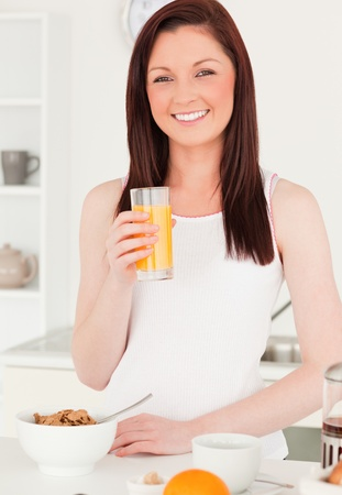 Young attractive red-haired woman drinking a glass of orange juice in the kitchen in her appartment photo