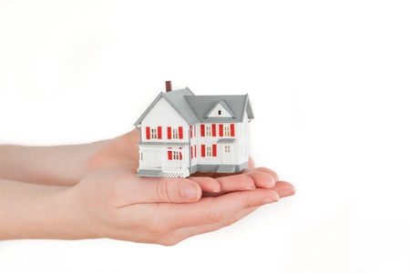 Hands holding a miniature house on a white background photo