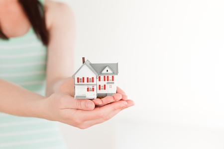 Female holding a miniature house while standing on a white background photo