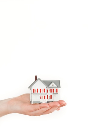 Hand holding a miniature house on a white background photo