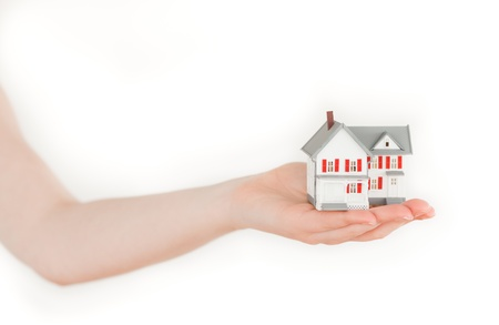 Arm holding a miniature house on a white background photo