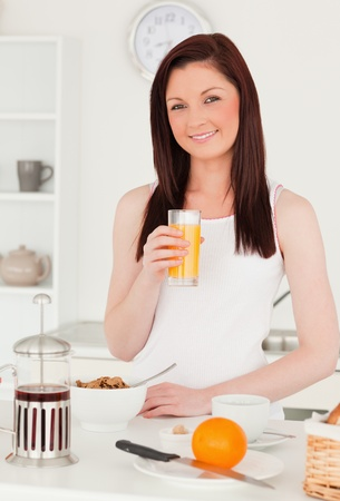 Young beautiful red-haired woman drinking a glass of orange juice in the kitchen in her appartment photo